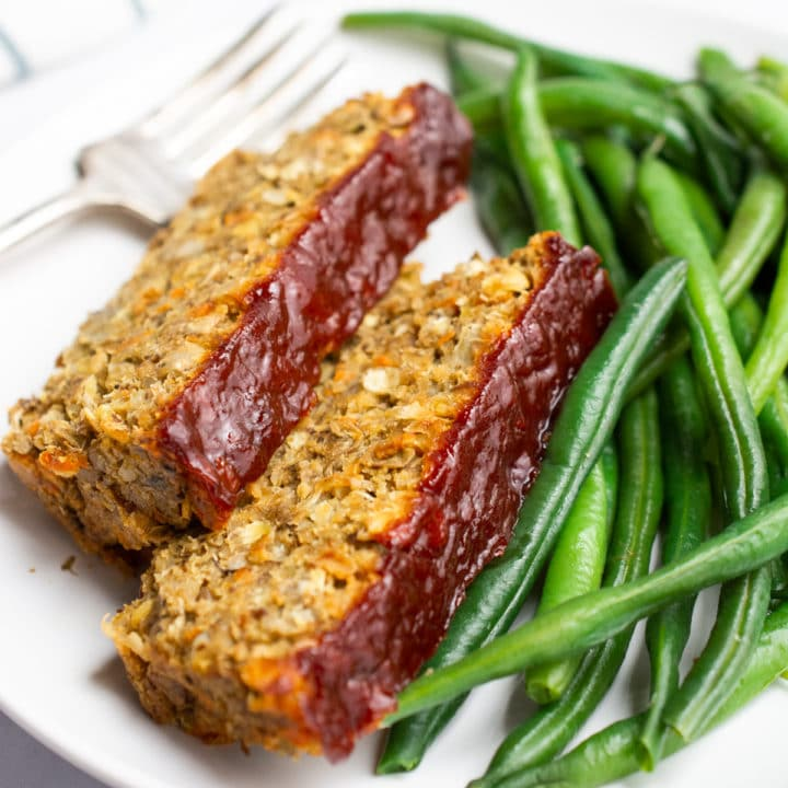 Vegan lentil loaf topped with ketchup and served with green beans.