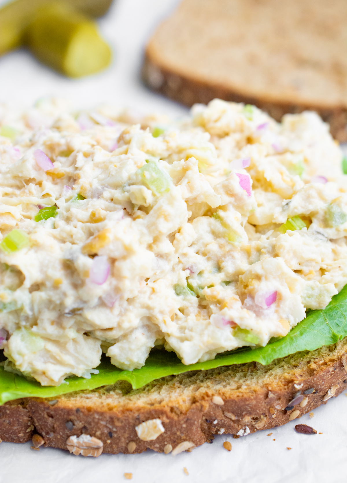 A slice of bread topped with lettuce and vegan tuna salad.
