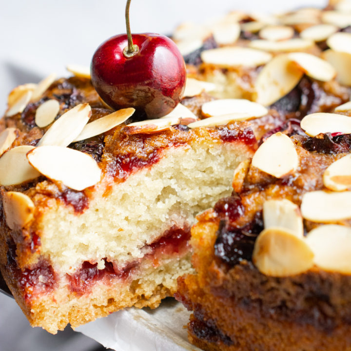 Vegan cherry coffee cake topped with toasted almond slivers.