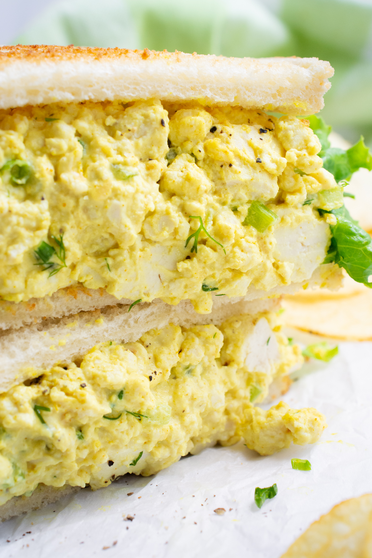 Vegan egg salad sandwich cut in half and stacked.