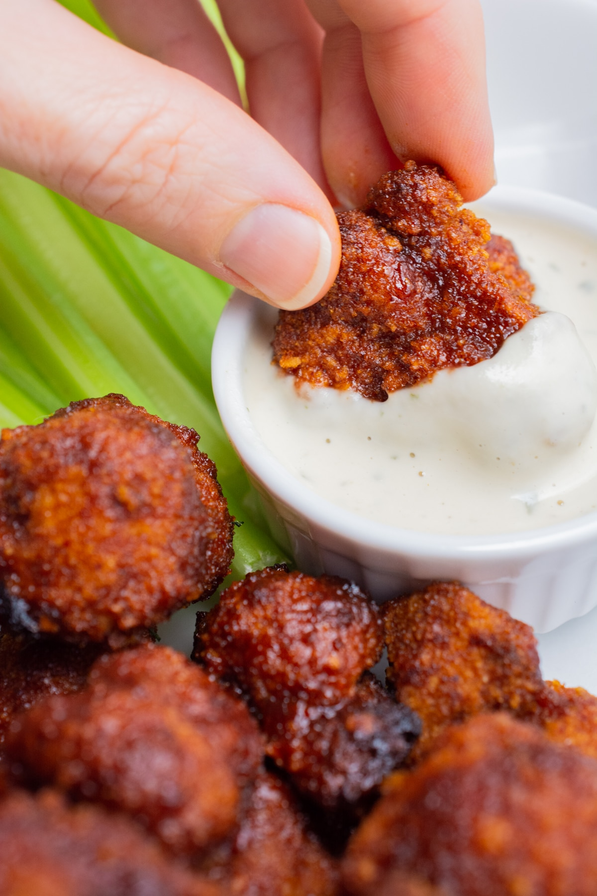 A hand dipping a BBQ Cauliflower wing in ranch.
