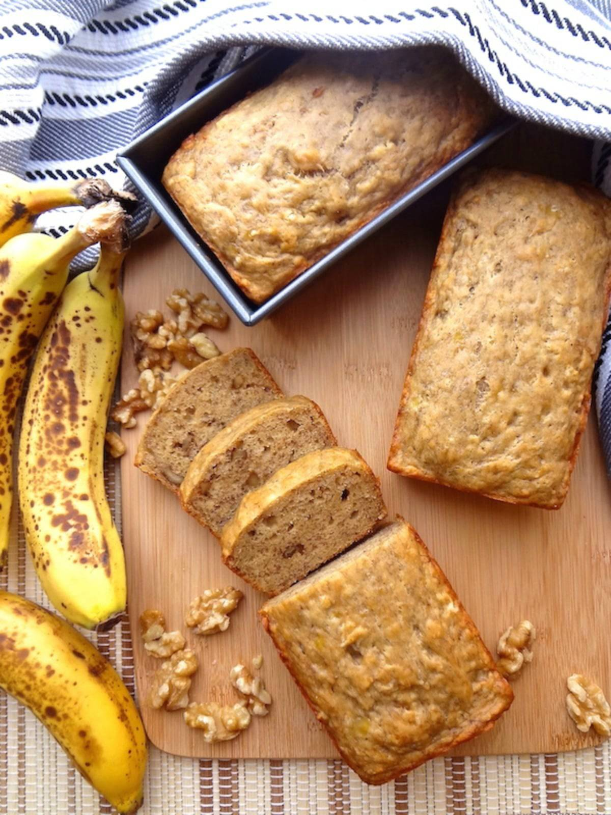 3 loaves of vegan banana bread.  One in the loaf pan, one whole, and the other with 3 slices cut.
