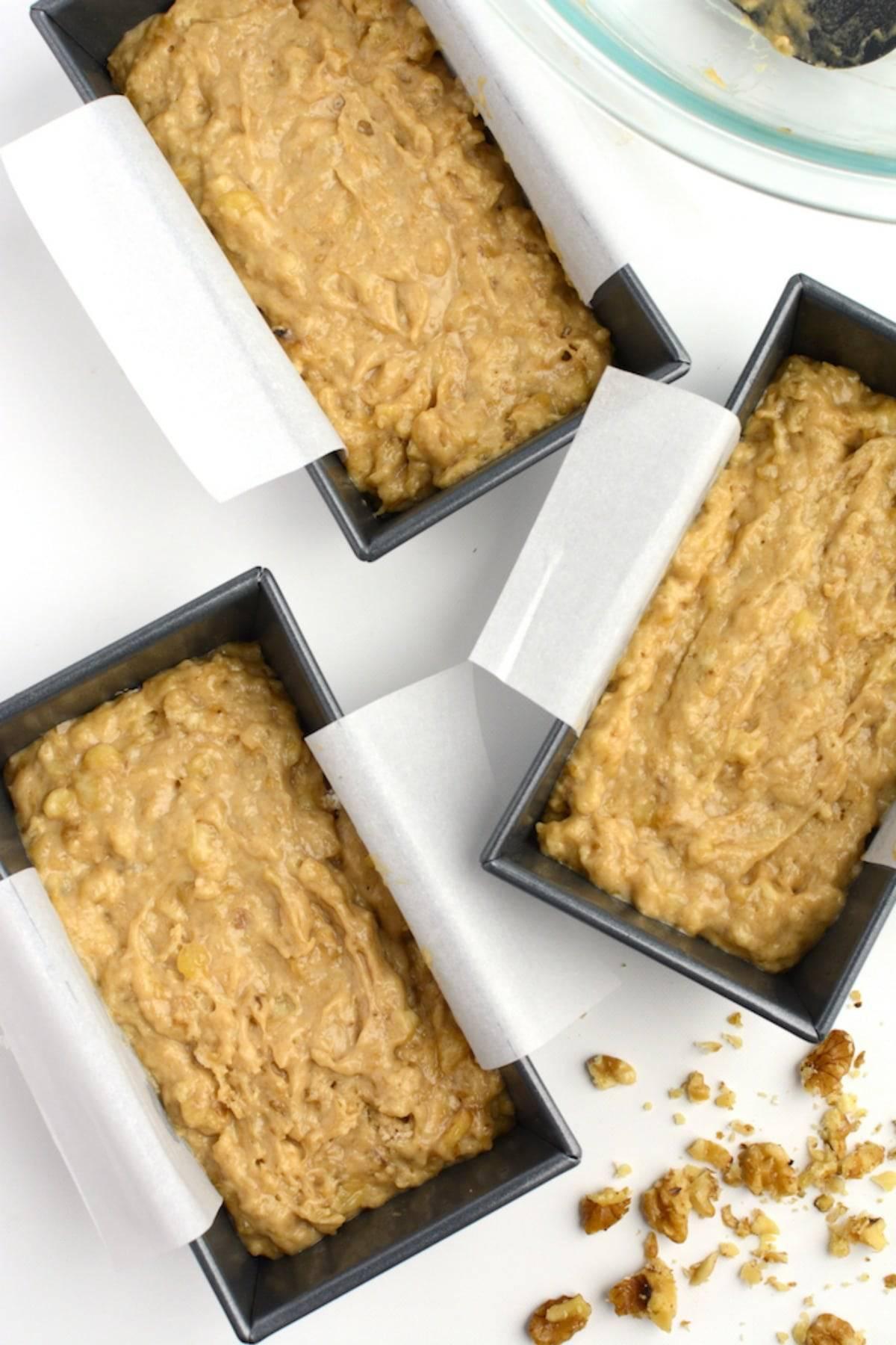 Vegan banana bread batter in mini loaf pans.