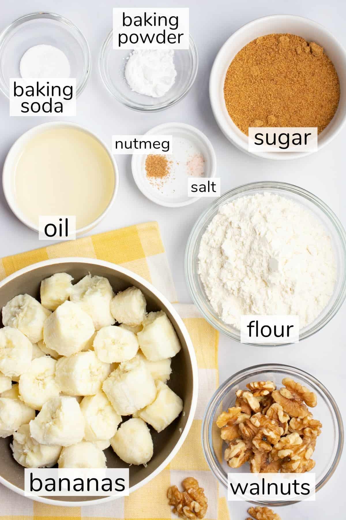 Labeled ingredients in bowls for vegan banana bread.