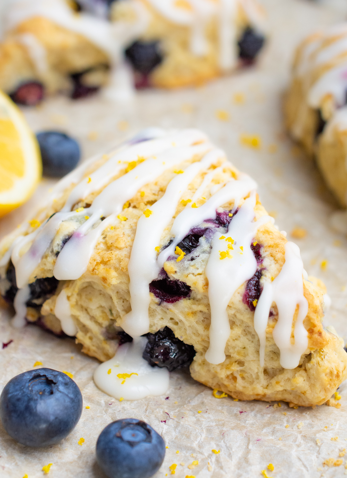 Vegan blueberry scone surrounded with lemon zest and blueberries.