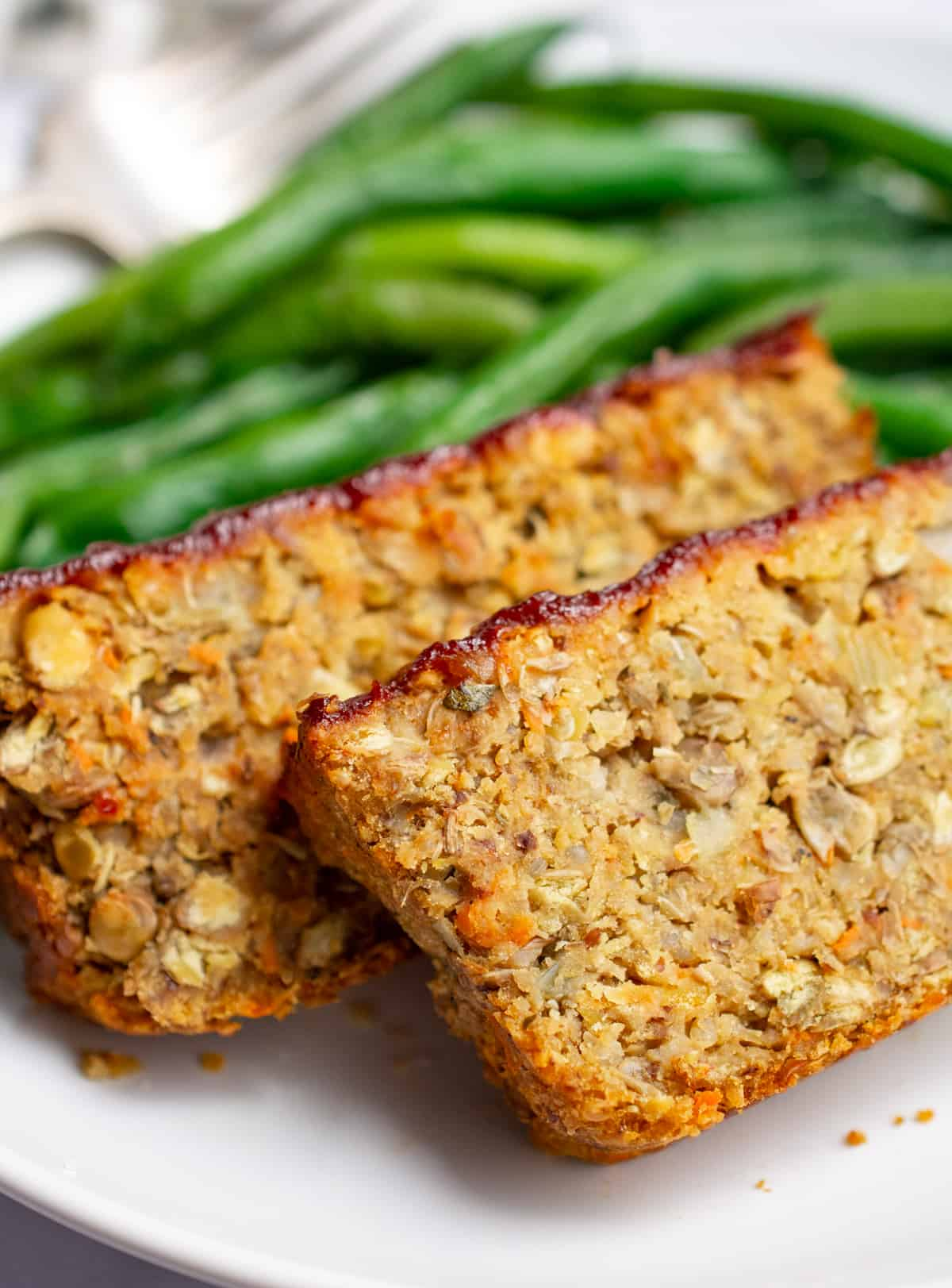 Close up of two slices of lentil loaf on a plate with green beans.