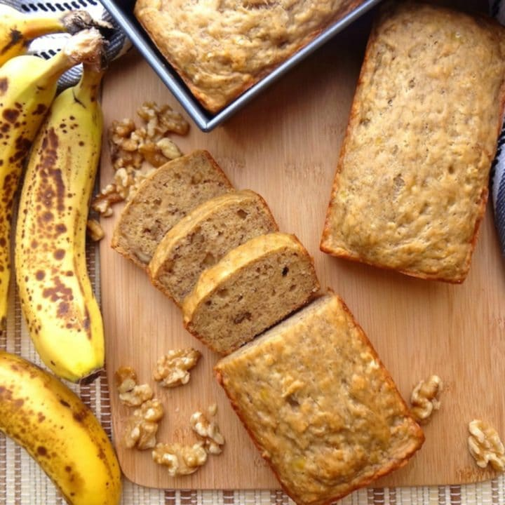 A mini loaf of vegan banana bread alongside ripe bananas and chopped walnuts.