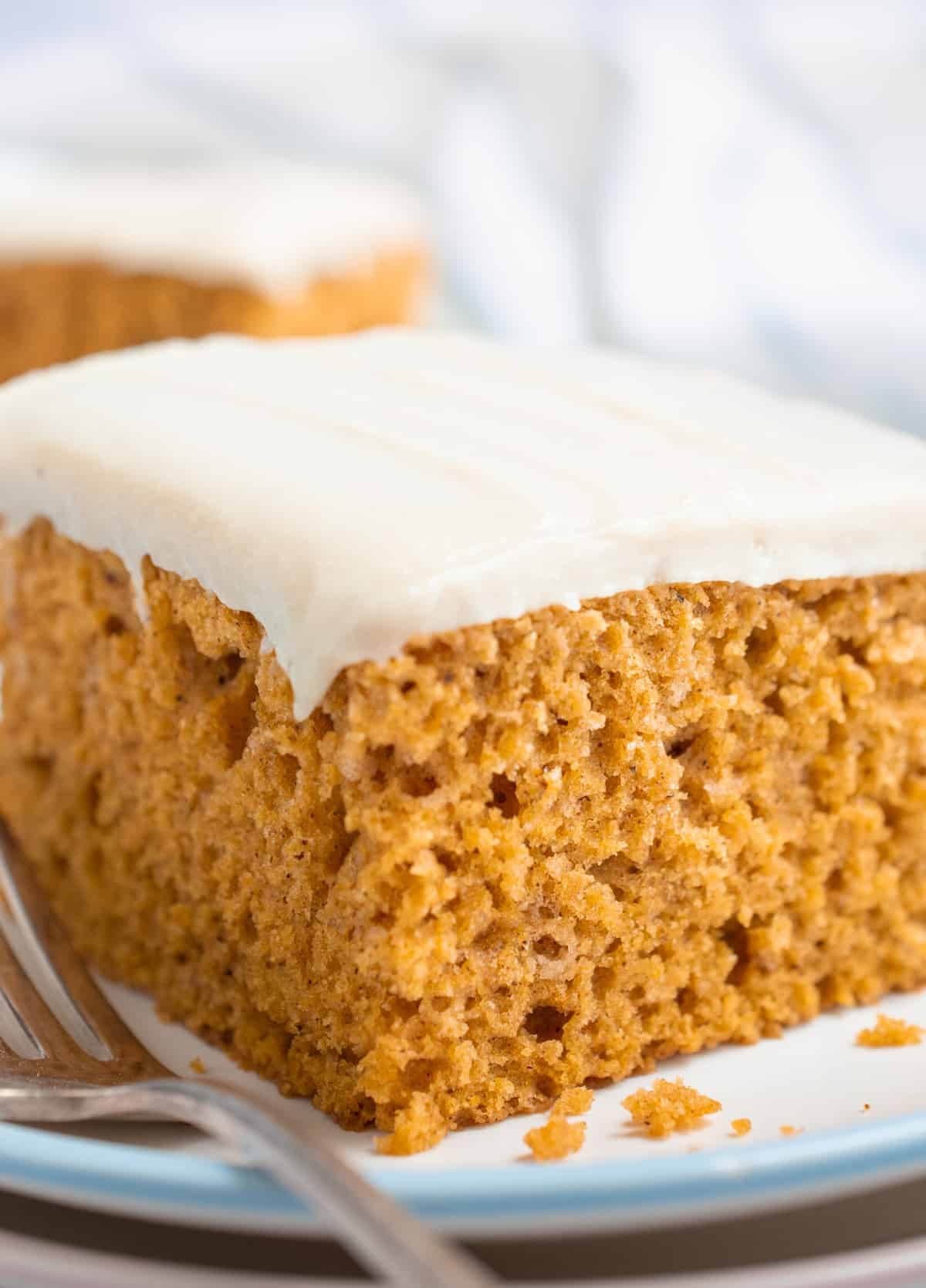 A slice of frosted vegan pumpkin cake on a plate with a fork.