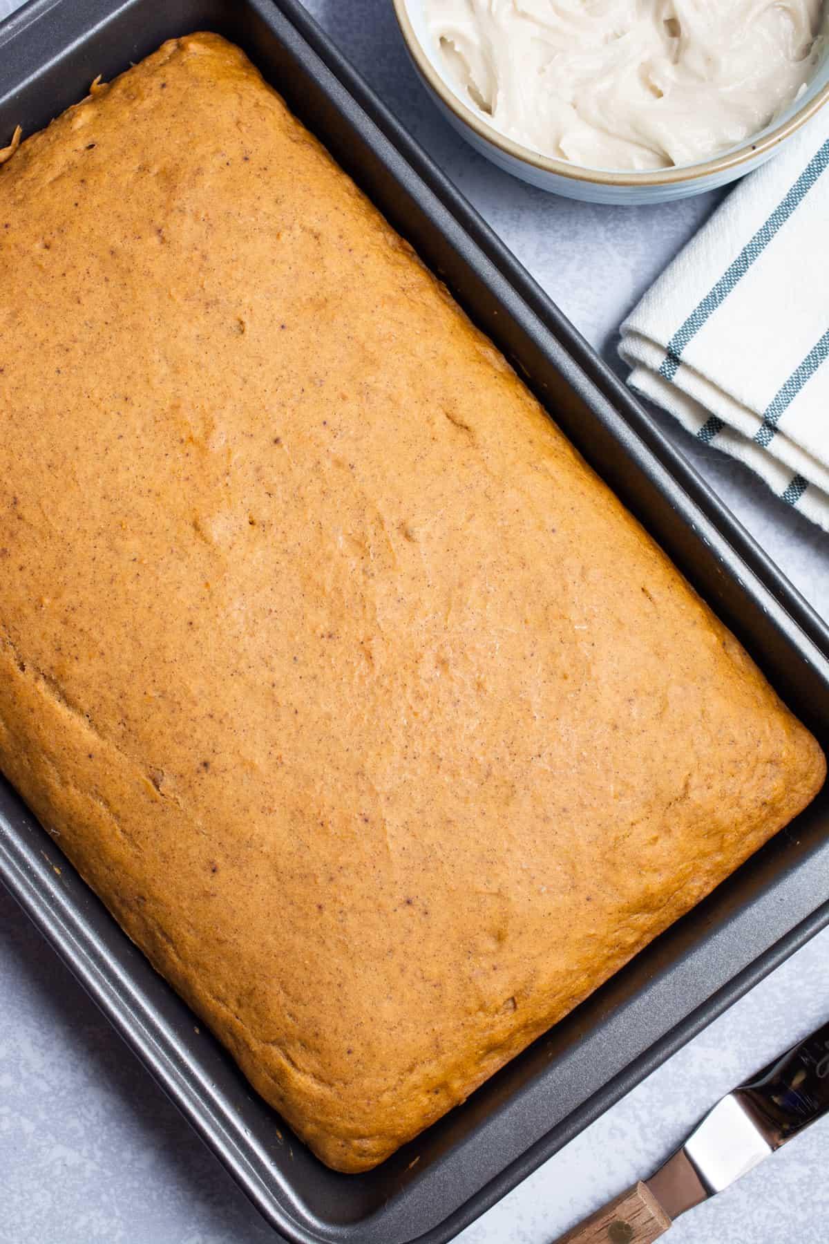 Freshly baked vegan pumpkin cake in a rectangle cake pan.
