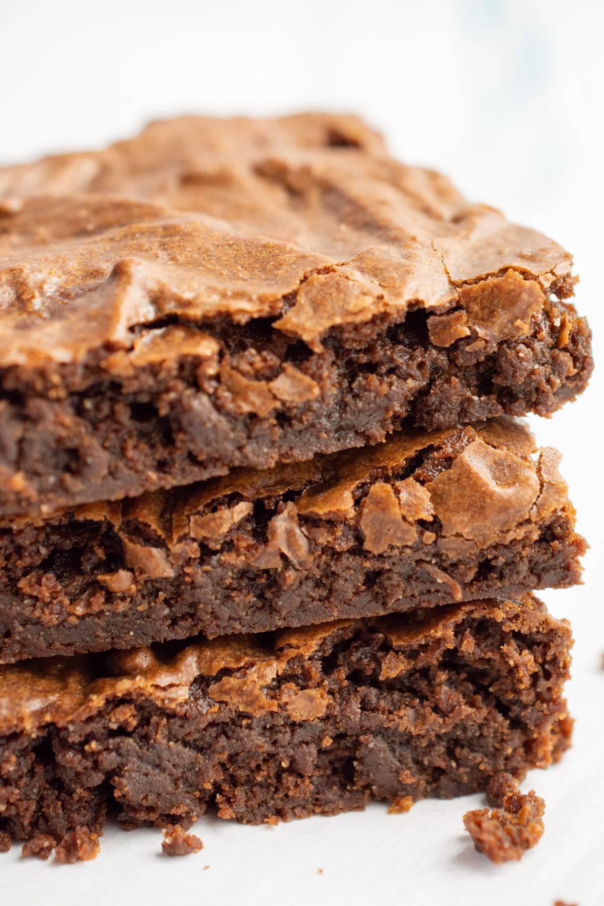 Three chocolatey vegan brownies stacked.