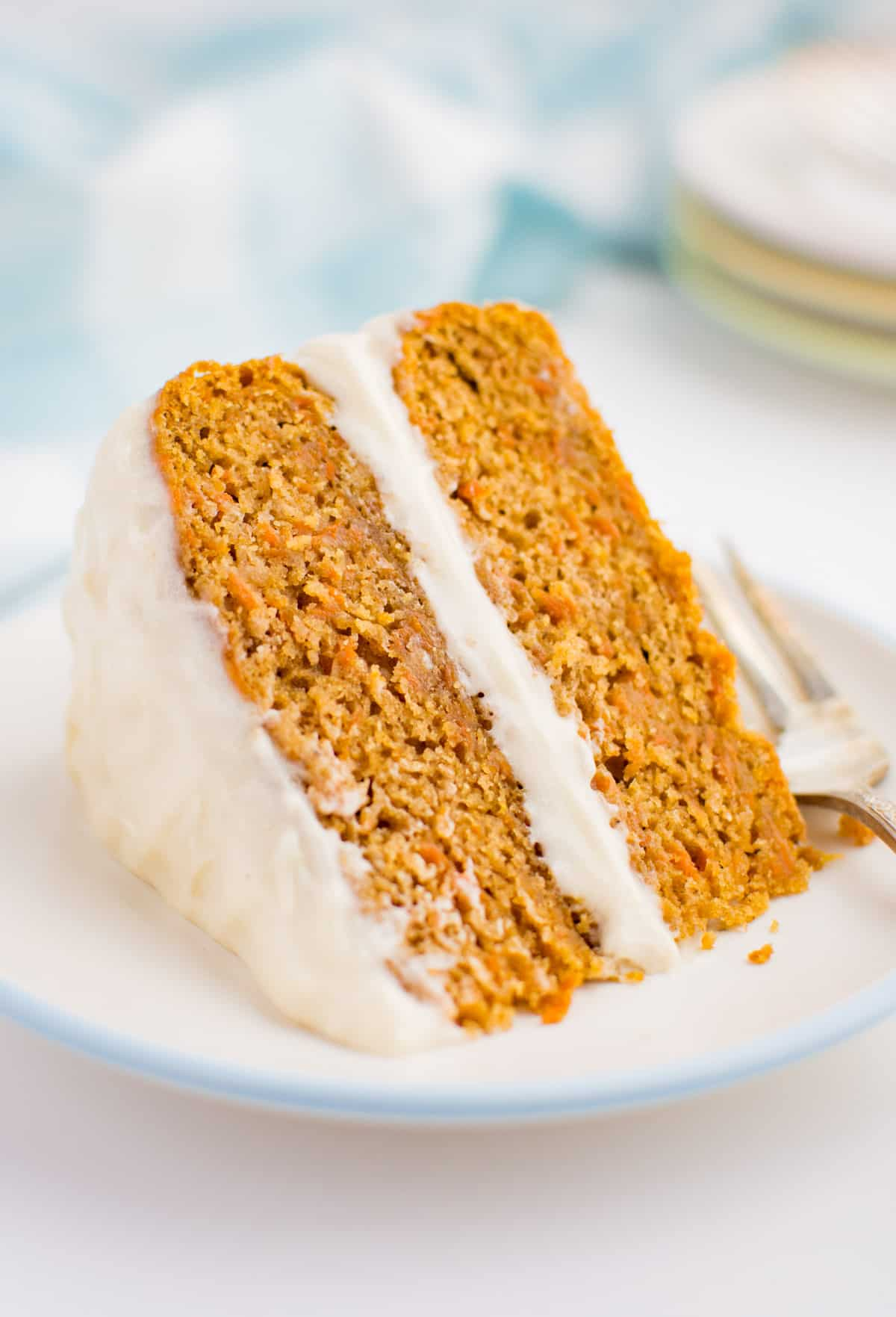 A wedge of 2 layer carrot cake with cream cheese frosting.