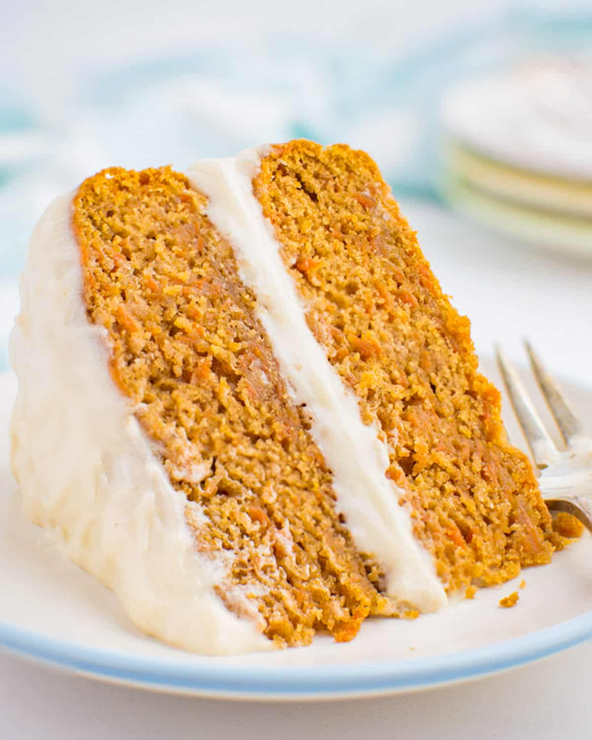 A plated slice of vegan carrot cake with cream cheese frosting.