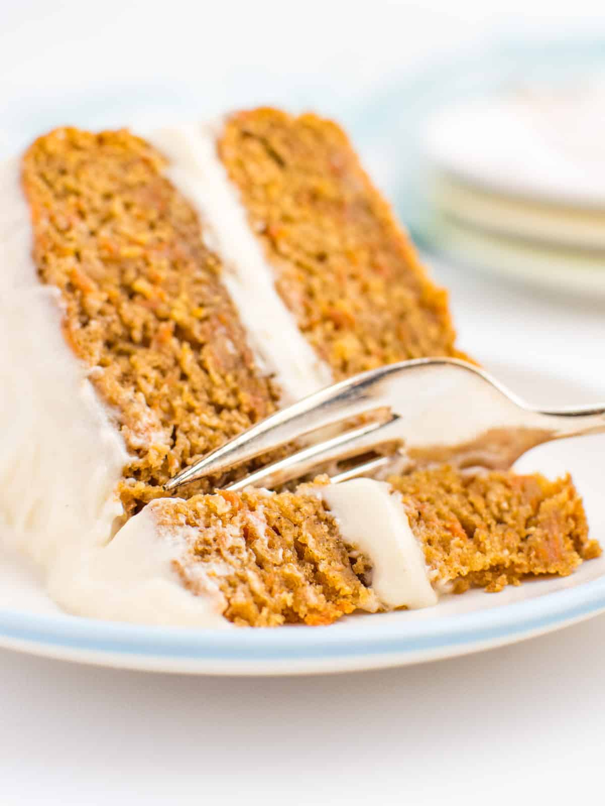A fork cutting into a slice of vegan carrot cake.