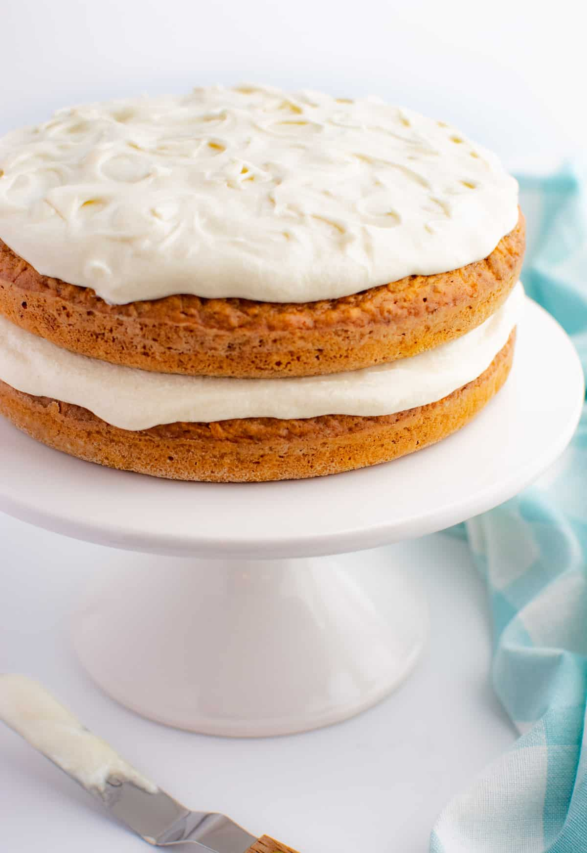 A 2 layer carrot cake with cashew cream cheese frosting on a white cake stand.