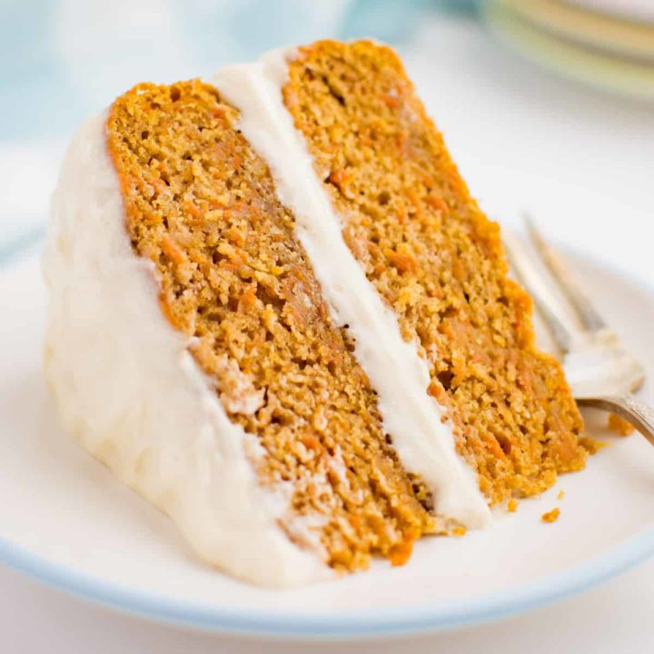 A wedge of 2 layer carrot cake with frosting on its side on a white plate.