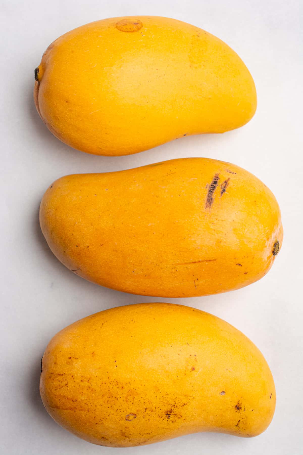 Three honey mangoes lined up on a white background.