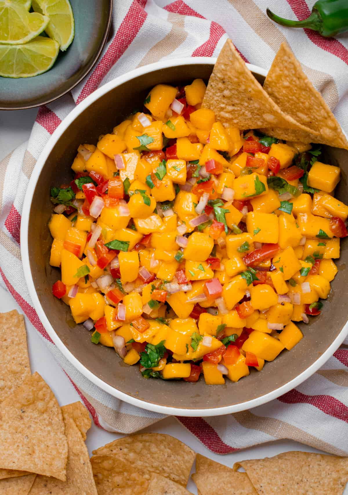 A brown bowl filled with mango salsa and surrounded by tortilla chips.