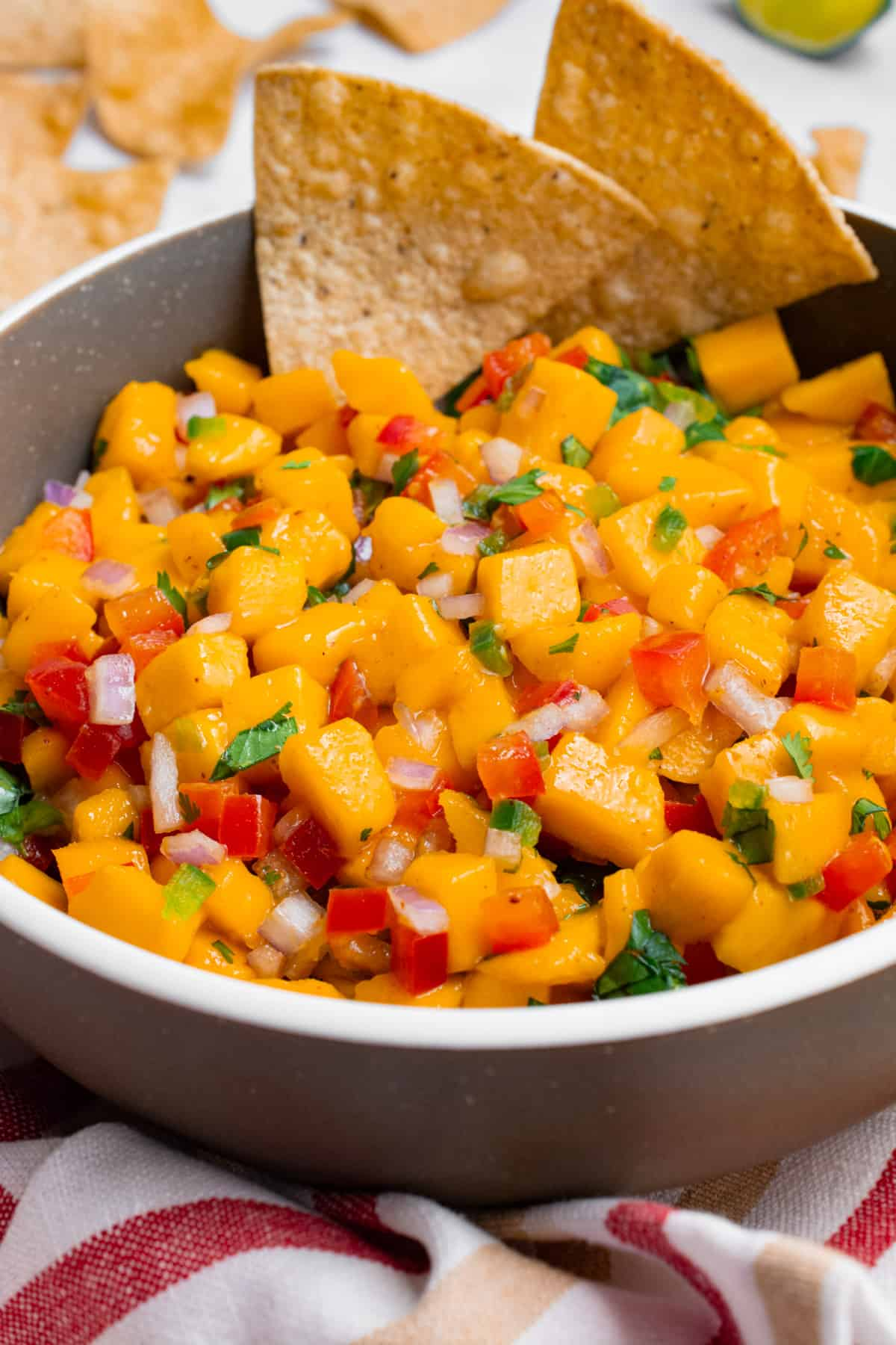 A bowl of mango salsa with 2 chips dipped in.