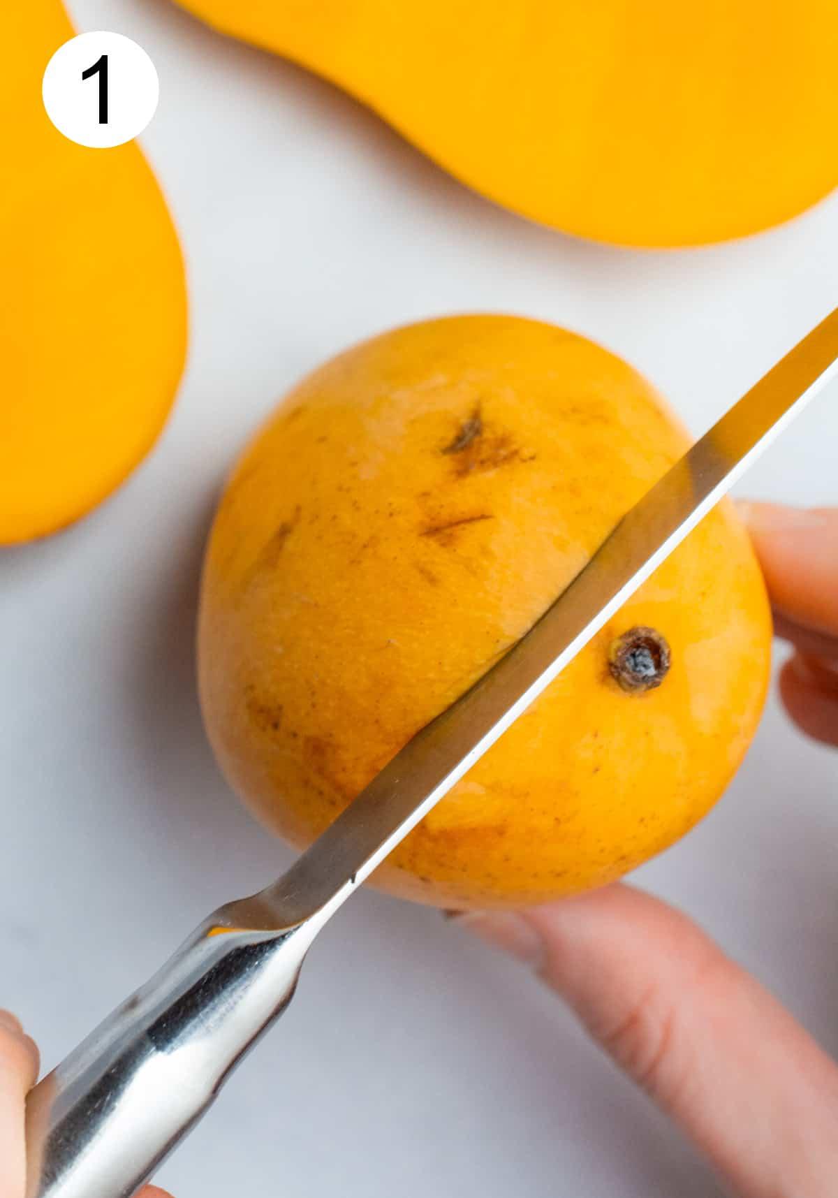 A knife cutting through one side of a honey mango.