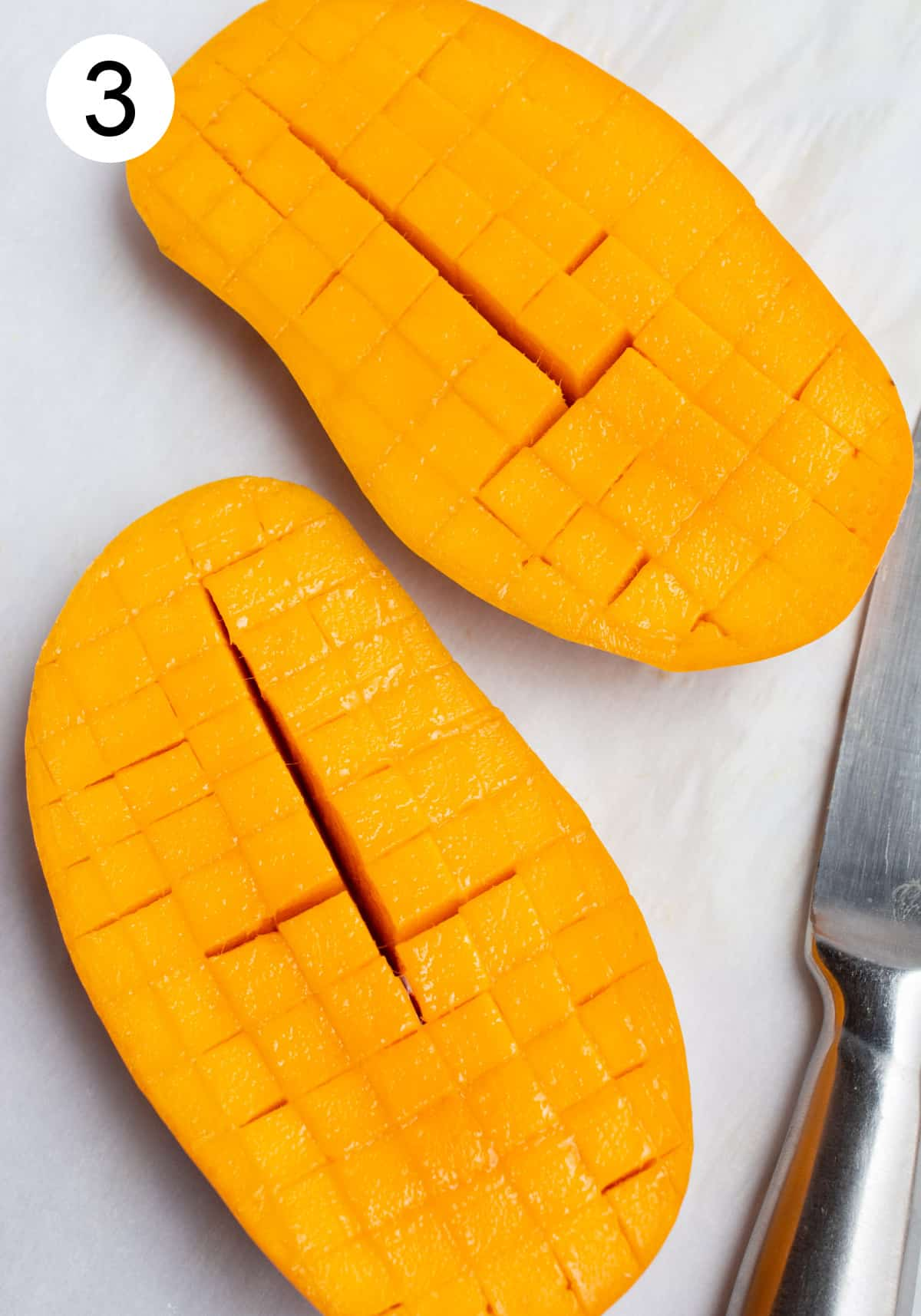 Two mango halves sliced into cubes in their skin.