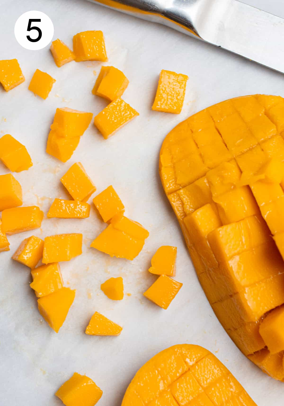 Cubes cut off of the mango skin laying on parchment paper.