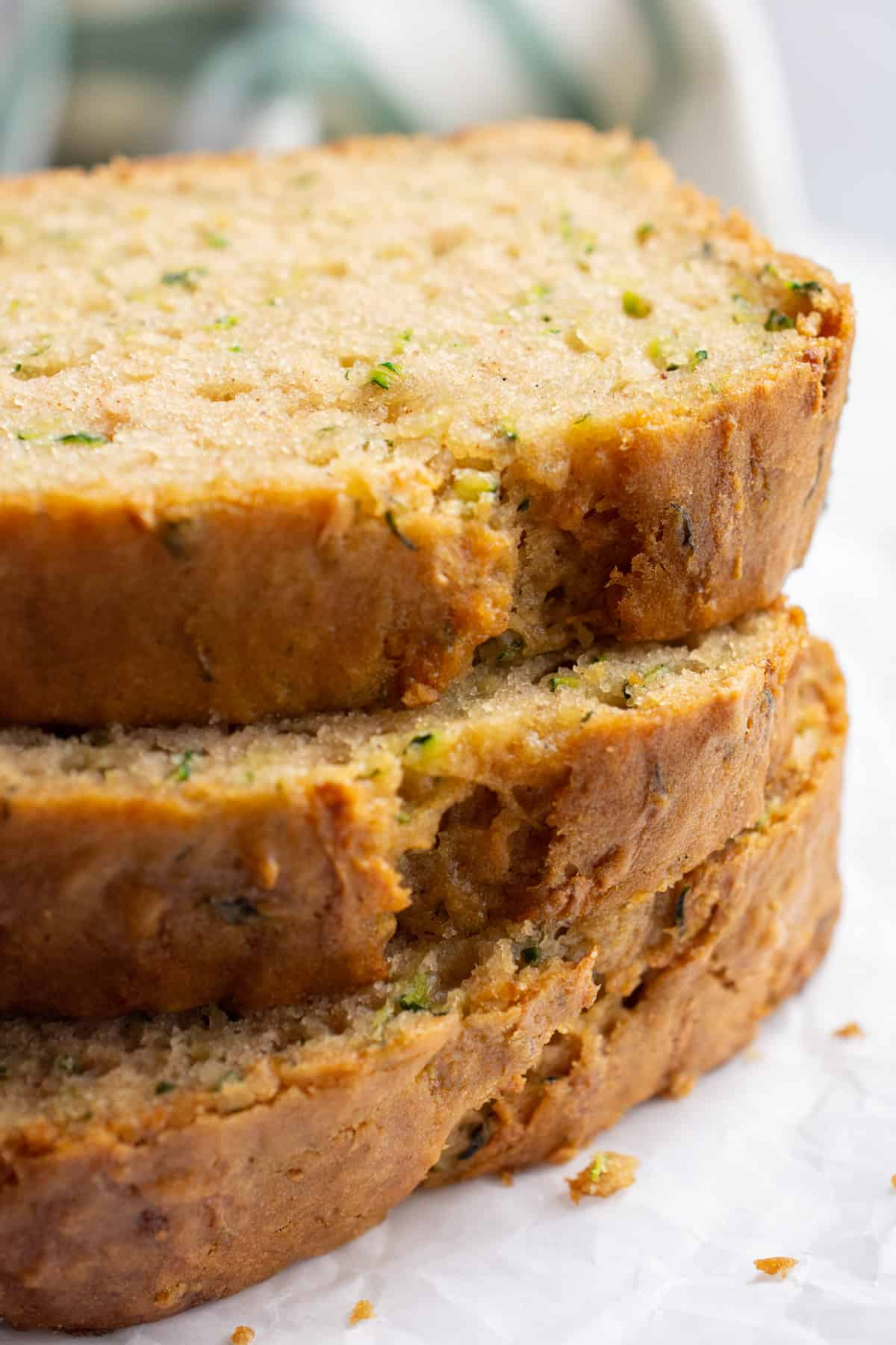 Three stacked slices of zucchini bread.