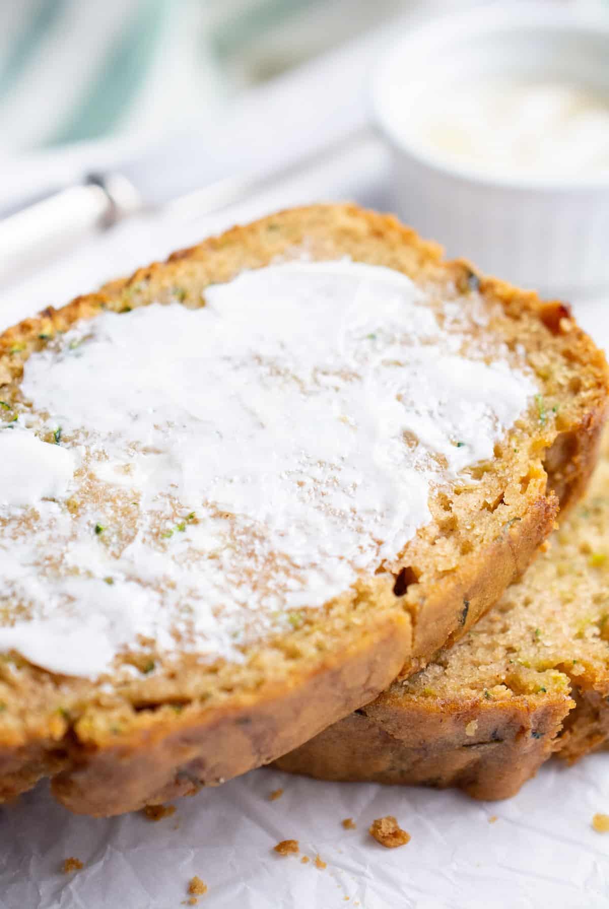A buttered slice of vegan zucchini bread.