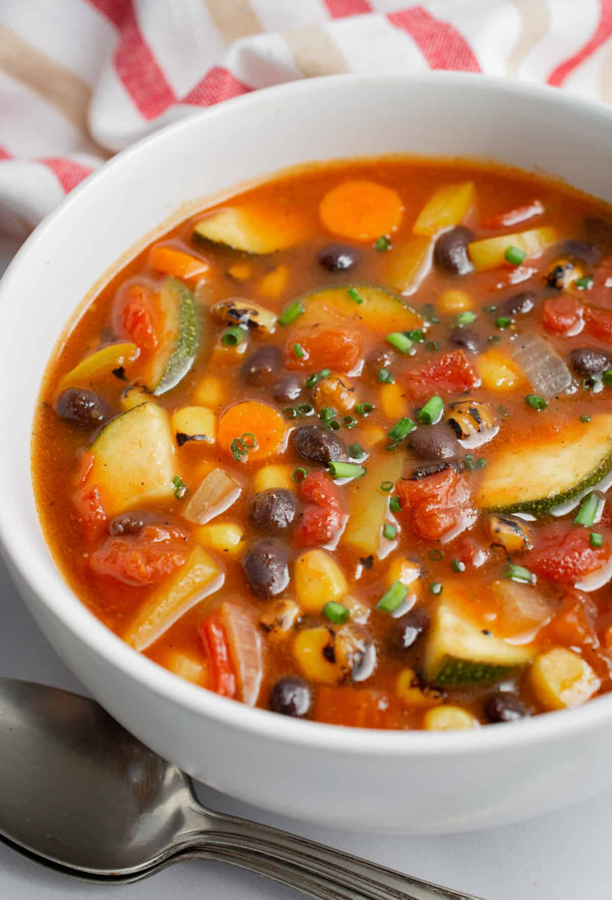 A bowl of vegan southwest vegetable soup with two spoons next to the bowl.